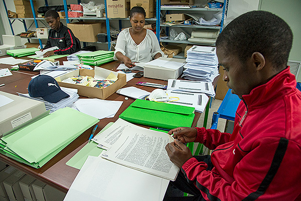 Earlier in the project, Phelelani Ntsikithi, Faith Marango and Sphelele Ntsikithi work on dividing manuscripts into the three workflows.