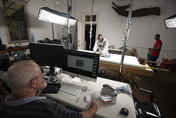Scott Cronwright looks on while Sandile Mhlongo loads a flat object to the capture surface and Timothy Zuma prepares the next object, Phansi Museum, Durban.
